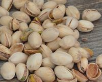 Pistachios some in the shell. Pistachios in and out of the shell on a wooden background stock photography