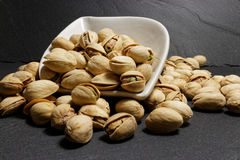 Pistachios in white bowl on black background Stock Images