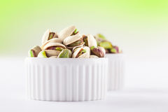 Pistachios on white in ceramic jars. Pistachios in two white ceramic jars on white and green background Stock Photos