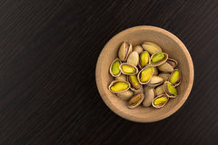 Pistachios. On wood plate ob dark wood table royalty free stock photography