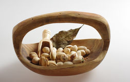 Pistachios in a wooden bowl. Pistachio is a small tree originating from Central Asia and the Middle East. In a 100 gram serving, pistachios provide 562 calories royalty free stock images