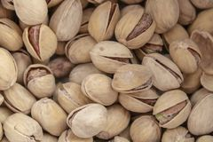 Pistachos abiertos deliciosos salados en un cuenco fondo natural marrón de nueces naturales imagen de archivo libre de regalías