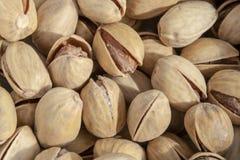 Pistachos abiertos deliciosos salados en un cuenco fondo natural marrón de nueces naturales imágenes de archivo libres de regalías
