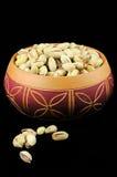 Pistachos en un tazón de fuente de cerámica Imagenes de archivo