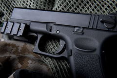 Pistal automatic short hand gun 9 mm. Pistal automatic short hand gun in the  US army prop background photo in lowlighting and dark shadow concept Stock Photo