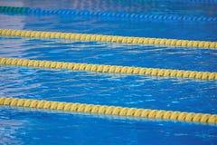 Pistas amarelas na água azul da associação Foto de Stock