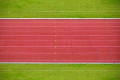 Pistas da pista de atletismo com grama verde Fotografia de Stock