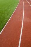 Pistas de borracha da pista de atletismo no estádio artificial da grama Imagens de Stock