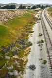 Pistas de ferrocarril abandonadas a lo largo de la zona costera pacífica que lleva en el horizonte Foto de archivo libre de regalías