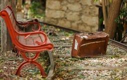 Pistas de ferrocarril, banco y una maleta vieja, retra Imagenes de archivo