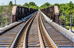Pistas de ferrocarril en la distancia y un caballete fotografía de archivo