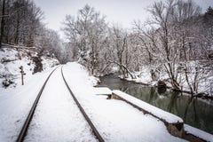 Pistas de ferrocarril nevadas y una cala en Carroll County rural Imagenes de archivo