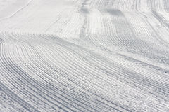 Pistas de la nieve en la cuesta hecha por Ratrack Imagenes de archivo