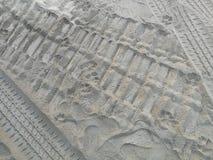 Pistas de la rueda y huellas del ser humano y del perro en la arena imágenes de archivo libres de regalías