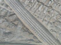 Pistas de la rueda y huellas del ser humano y del perro en la arena fotografía de archivo