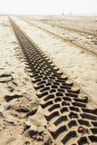 Pistas de neumáticos de un vehículo motorizado en la playa, los modelos artificiales y las estructuras imágenes de archivo libres de regalías