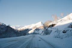Pistas del camino y del coche de la nieve en el camino en el invierno en el Cáucaso del norte Árboles y montañas nevados El conce Imagen de archivo