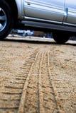 Pistas del coche en la arena Fotos de archivo libres de regalías