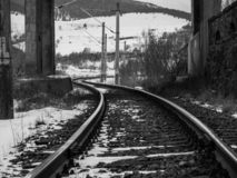 Pistas del ferrocarril debajo de un puente concreto en el invierno fotos de archivo