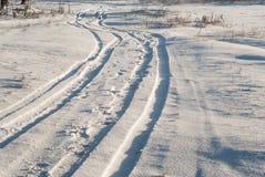 Pistas del neumático de coche en nieve Imagenes de archivo