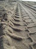 Pistas del neumático en el arena de mar (ascendente cercano) 3 Fotos de archivo libres de regalías
