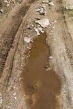 Pistas del neumático en el camino de tierra fangoso Imagen de archivo libre de regalías