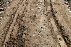 Pistas del neumático en el camino de tierra fangoso Fotos de archivo libres de regalías