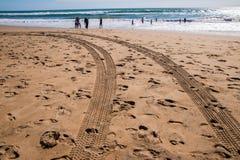 Pistas del neumático en el título de la playa hacia el océano por donde hay gente y en el agua imagenes de archivo