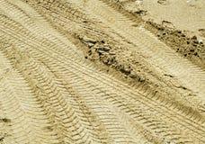 Pistas del neumático en la arena Imagenes de archivo