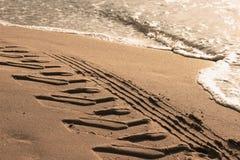 Pistas del neumático en la arena cerca del mar Fotos de archivo libres de regalías