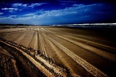 Pistas del neumático en la playa Imágenes de archivo libres de regalías