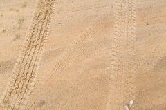 Pistas del neumático en el camino de tierra amarillo marrón seco Foto de archivo libre de regalías