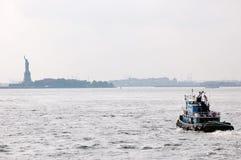 Pistas del remolcador del AA hacia la isla de la libertad Imagenes de archivo