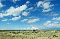 Pistas y coches en un largo camino al horizonte del cielo Fotos de archivo
