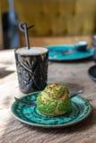 Pistascheclair, profiterole i glasyr på den gröna plattan på tabellen, slut upp Eclair vaniljsås som är syrlig med pistaschkräm t royaltyfri fotografi