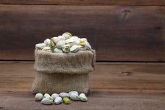 Pistaschmuttrar i säckväv plundrar på träbakgrund Royaltyfria Foton