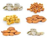 Pistaschmuttrar, mandlar, jordnötter på vit bakgrund Arkivfoton