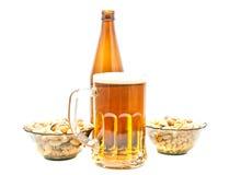 Pistazien, Erdnüsse und helles Bier stockfotografie