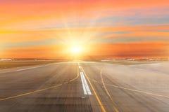Piste à l'aéroport l'horizon au coucher du soleil au centre des rayons légers du soleil Photo libre de droits