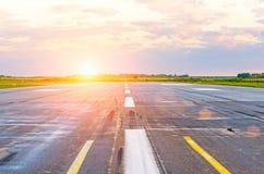 Piste à l'aéroport pendant le matin à la lumière du soleil de coucher du soleil d'aube Photographie stock libre de droits