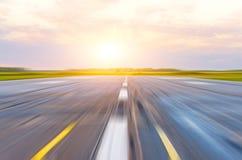 Piste à l'aéroport pendant le matin à la tache floue de mouvement de lumière du soleil de coucher du soleil d'aube Photo stock