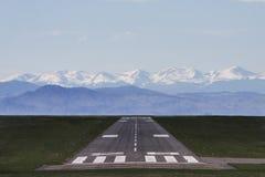 Piste d'aéroport avec des montagnes à l'arrière-plan Images stock