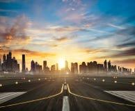 Piste d'aéroport avec la ville moderne sur le fond dans la lumière de coucher du soleil Photographie stock libre de droits