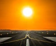 Piste d'aéroport avec le grand soleil dans la lumière de coucher du soleil Image libre de droits