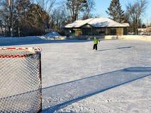 Piste de hockey sur glace extérieure dans la fin de l'après-midi avec de longues ombres photos libres de droits