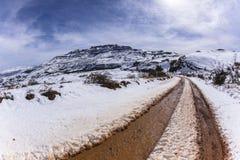 Piste del fango della strada non asfaltata della neve della montagna Fotografia Stock