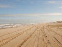 Piste dell'automobile sulla sabbia fotografia stock