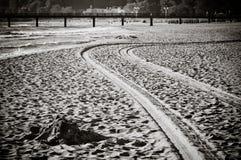 Piste di legno del pneumatico e del pilastro nella sabbia sulla spiaggia Immagine Stock