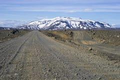 Piste di sporcizia islandesi con il vulcano giusto nei precedenti Fotografie Stock