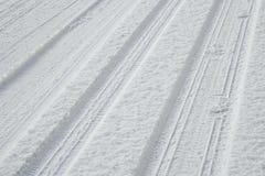 Piste e footstepts della gomma su neve fresca Fotografia Stock Libera da Diritti